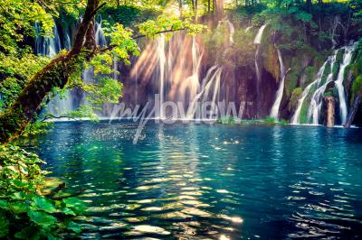 Wall mural Last sunlight lights up the pure water waterfall on Plitvice National Park